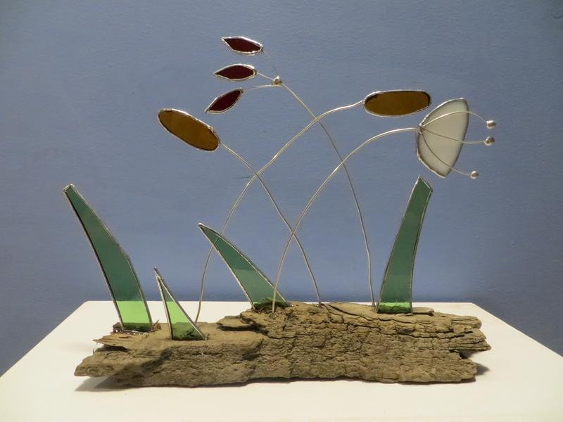 A 2 d glass white flower, red sumac leaf, 2 cattails, with grass pieces set into a piece of driftwood.
