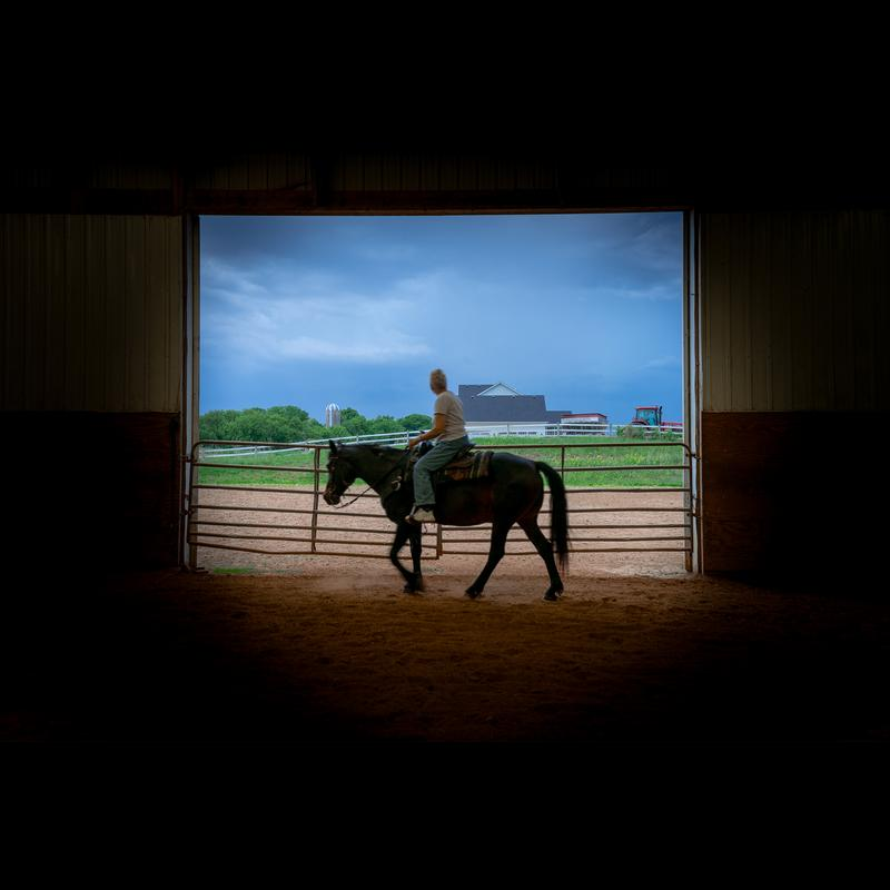 A grandmother wearing old jeans and a plain gray shirt rides on a dark brown horse inside a horse arena. They are moving past the open barn doors, the light from outside making the arena look dark. The grandmother is looking out the doors at a field with a silo, red tractor, white building, trees, and white fence in the background. The sky is a gray blue with dark clouds rolling in right before a storm. The horse's hooves kick up dirt from walking creating a light cloud of dust on the ground. The grandmother and the horse are slightly blurred from movement while everything around them is clear.