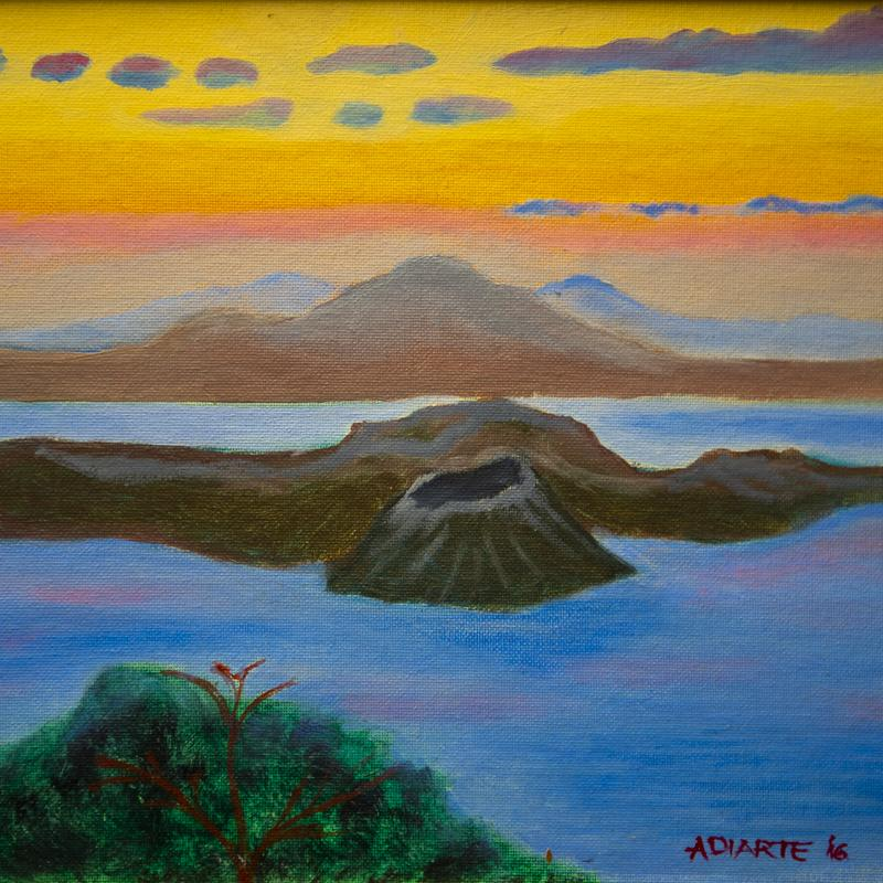 Painting of a volcano, a large caldera surrounded by Taal Lake in the Philippines.  In the background are overhead grayish and blue clouds, multi-colored sky ranging from glows of yellow to orange to red.  There are also receding distant mountains. The foreground shows some greenery and a reddish tree.
