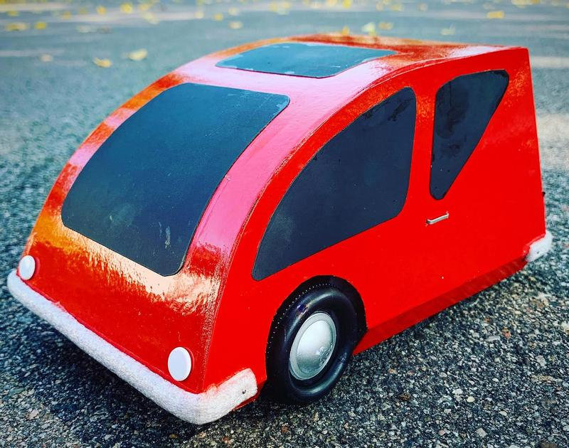 Sculpture of a red car made out of cardboard and plastic bottle caps sitting on a street.