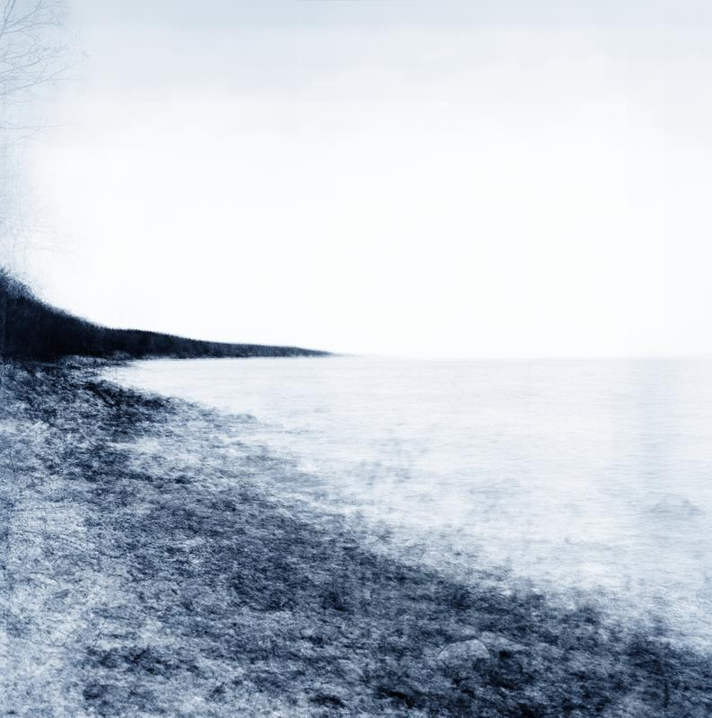Landscape photograph in shades of blue showing the shore of Brighton Beach and Lake Superior. The image is created by layering many images of the same place taken at different times throughout a year, giving it an ethereal feeling.