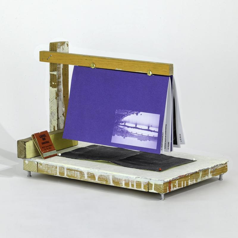 A small sculpture with a base comprised of a wooden panel raised by push pin feet with scaffolding of painted wood suspending a blue pamphlet over the base forming a triangular wedge that hovers over black rectangle of sandpaper.