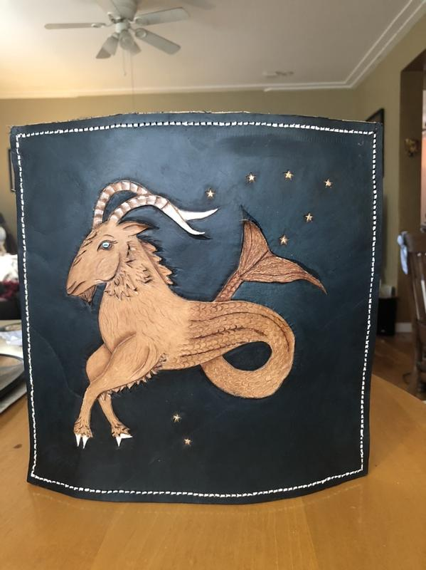 Capricorn Goat hand tooled and textured in leather with constellation in a blue black sky.