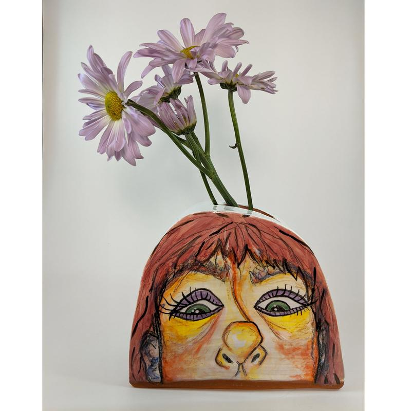 Purple daisies emerge from a dome shaped ceramic vase with a face painted on the surface from the nose up using reds, oranges, yellows, blues, and purples in the skin tones, with green eyes, surrounded by pink hair with short bangs over the forehead.