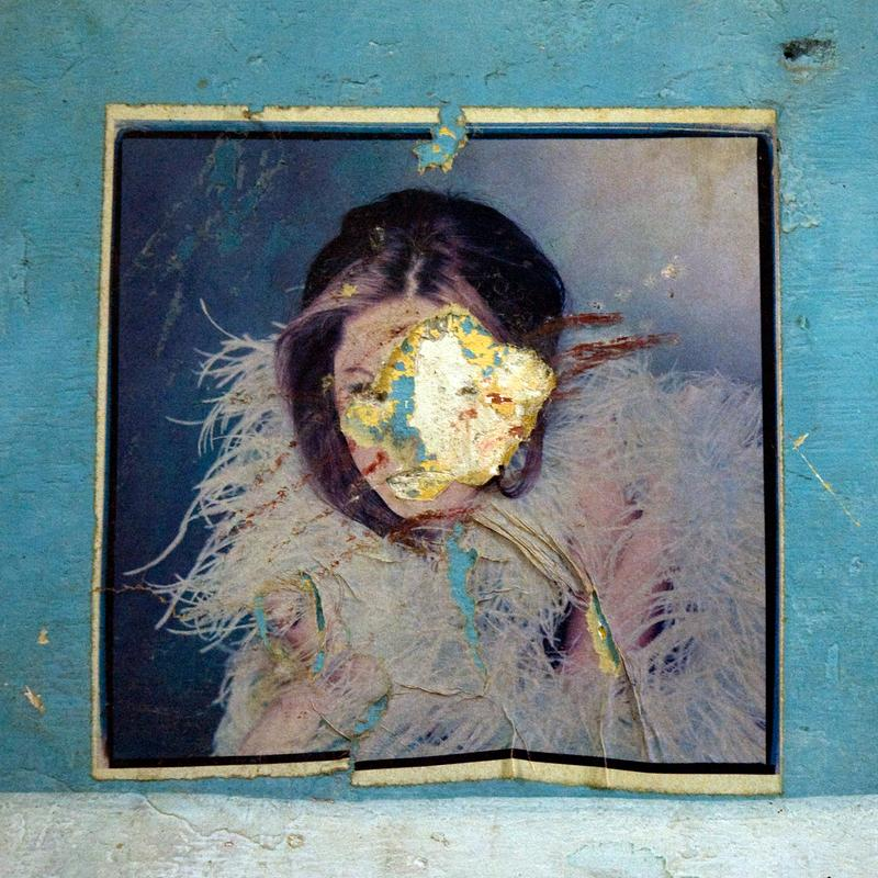A picture of a dark-haired woman cloaked in feathers adorns a plaster wall. The paper has been torn or worn so that her face is obscured.