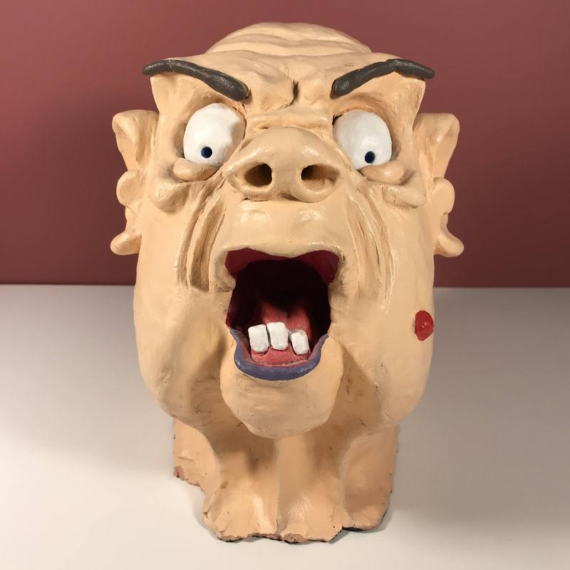 A ceramic sculpture of a hairless peach-skinned woman captured in an angry outburst, wearing purple lipstick and red rouge highlighting the beauty mark on her left cheek.