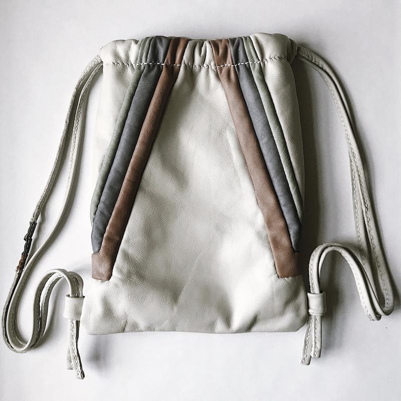 The design for this bag was inspired by the subway system in Stockholm, Sweden and pulls the color palette of pastel salmon, lavender, mint and white found in the Morby Centrum underground station. This piece is a handcrafted reversible leather backpack, with diagonal pastel stripes on one side, connecting to the opposite side where the stripes are horizontal. Above the horizontal stripes showcases the architectural insignia logo for the Minneapolis based minimal leather goods brand, Montgomery Collection. This drawstring backpack cinches at the top and includes details of the stripes on one side of the pull strings. The interior is lined in grey suede, soft to the touch and will protect all of your belongings held inside. Worn on either the diagonal or horizontal side, this backpack is a functional piece of art.