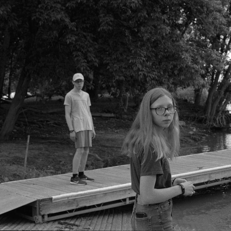 Black and white photograph with one teen, close-up in foreground, and one teen in background standing on water dock. Both subjects looking into the camera lens.
