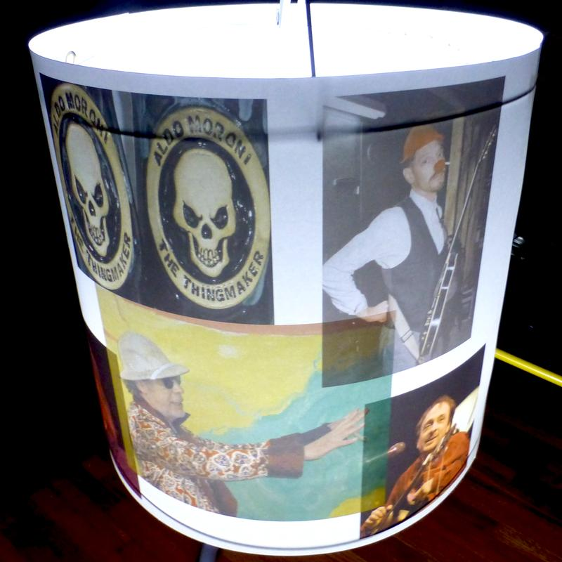 Cylindrical lampshade featuring a photo collage with images of Bruce Allen, Vic Chesnutt, Willie Murphy, and Aldo Moroni all gone now, illuminated from within. Yes this is a second photo. It's not that I think so much of myself or it  but I just think a 3D piece needs another angle.  thanks