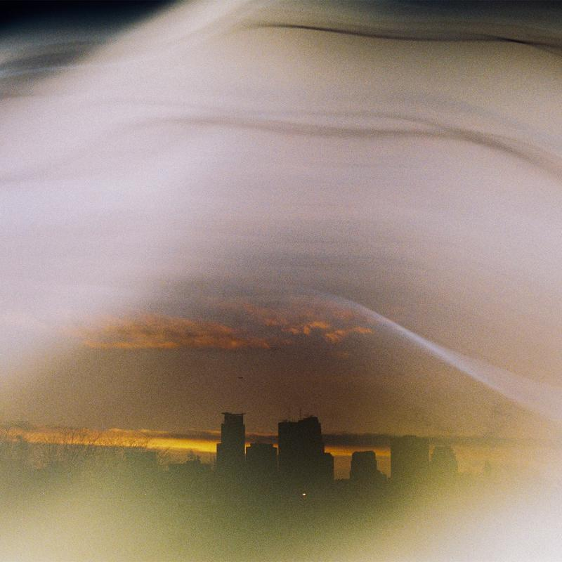 A decaying photo of the Minneapolis skyline, taken as the Winter sun sets the horizon ablaze in Midwestern reds and oranges, hidden under paths of grain-filled streaks of light, shifting the warm colors to whites, blues, greys and violets that cover the sky.