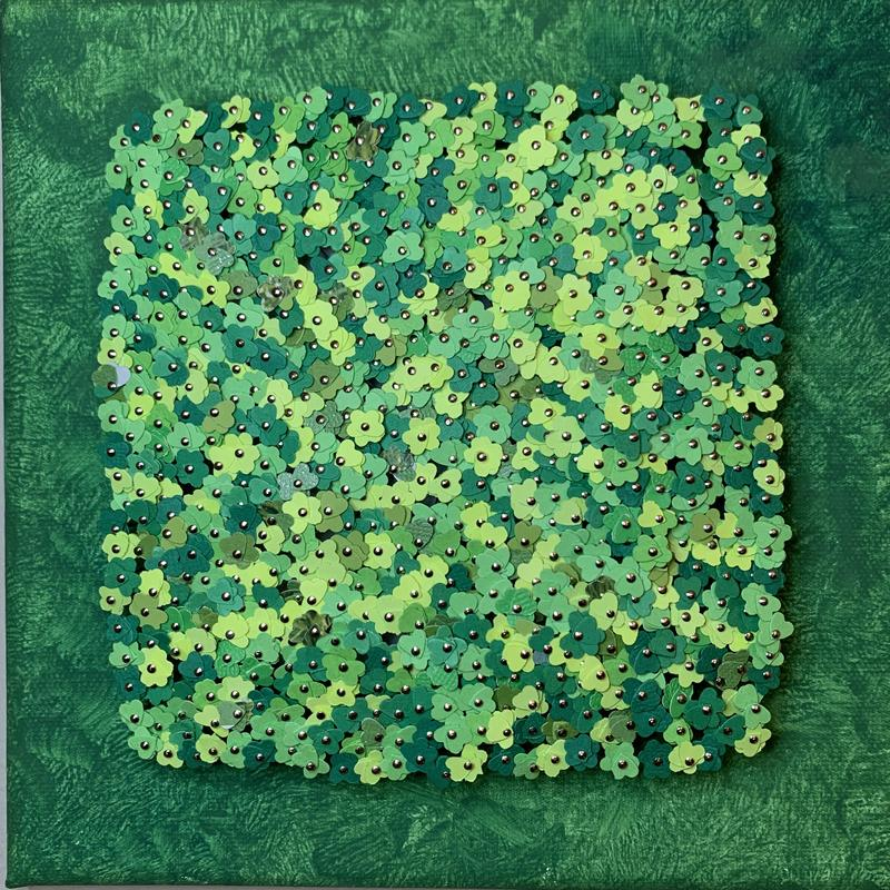 Tiny green paper cutouts on heads of pins, to form a mass gathering of 4 leaf clovers