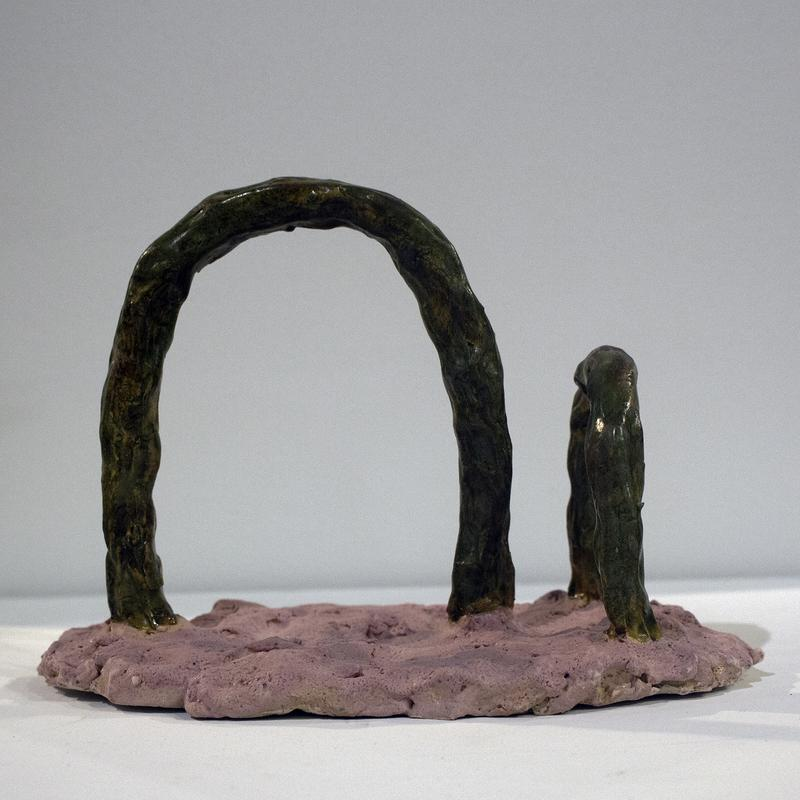 A non-objective ceramic form rendering the artists perception of a human relation. Two glossy green arches opposing each other in direction and size sit on top of a matte pink bumpy base. The color and form play at duality.