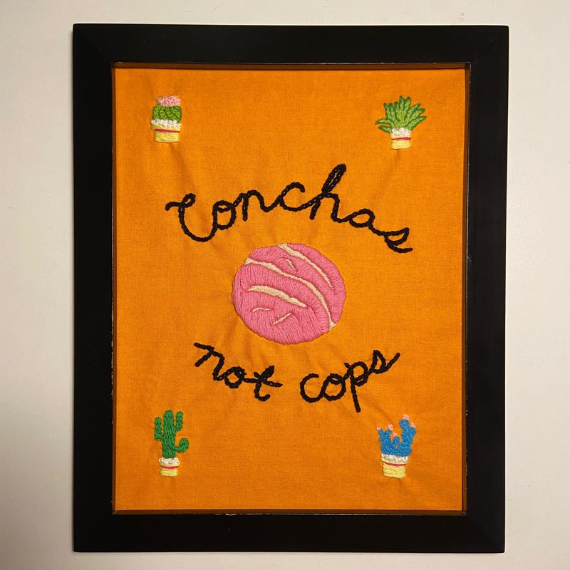 """An orange fabric background with a pink concha embroidered in the middle, and the text """"Conchas"""" above it and """"not cops"""" below it, embroidered in black cursive. Each corner has a different succulent in a yellow pot with a pink stripe (green round one with pink flower in the top left, green and leafy in the top right, green tall standard cactus in the lower left, and blue cactus with pink flower buds on the bottom right). It is in a dark brown, almost black, frame against a white background."""