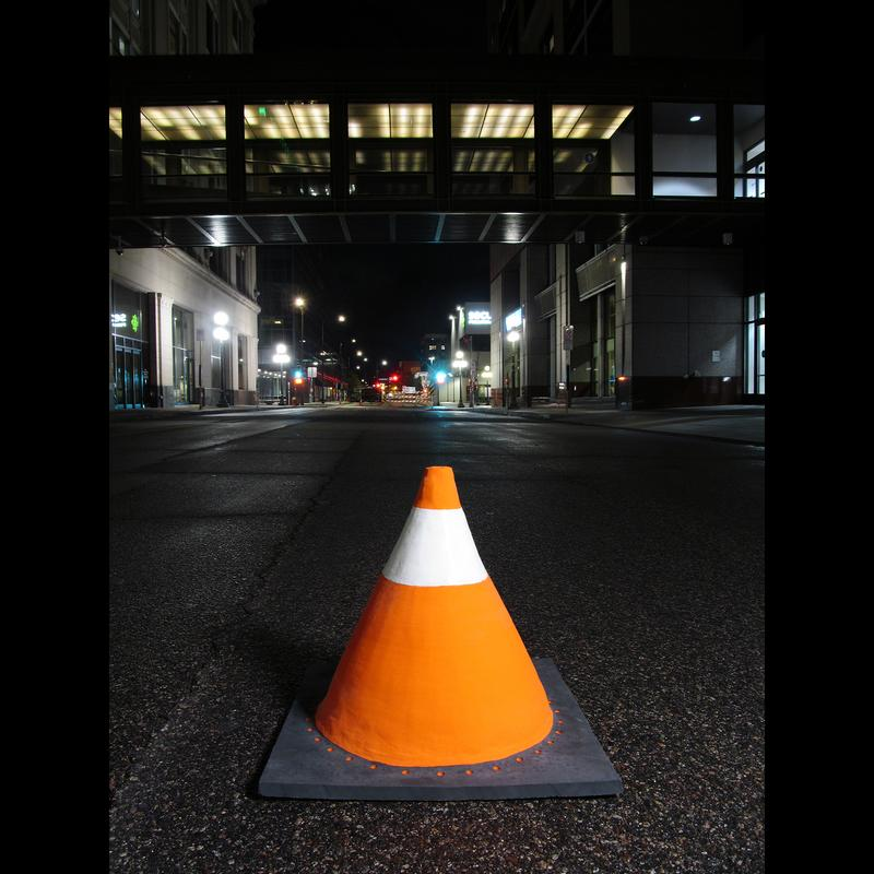 A photograph of an orange, black, and white ceramic facsimile of a traffic cone sitting in the middle of a city street at night.