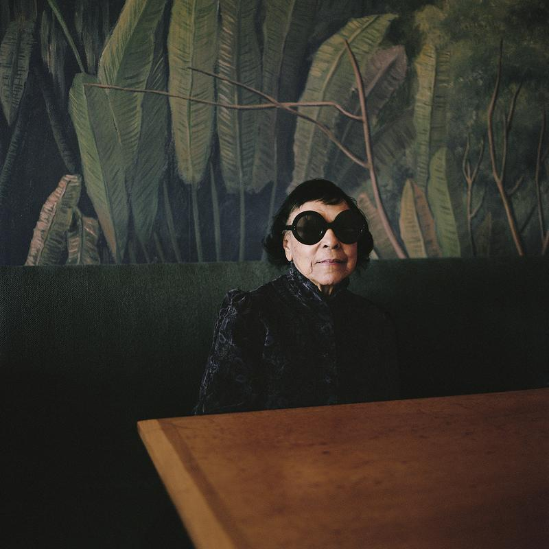 This is a portrait of an older woman. She is seated at a table on a plush green bench. Behind her is wallpaper with large green palm fronds printed on it. She is wearing a purple velvet dress and dark sunglasses.