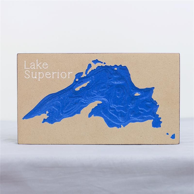 A wood engraving of Lake Superior with 3 dimensional depth and color.