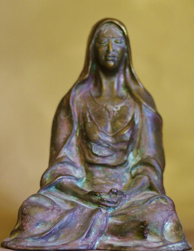 A bronze female figure seated cross-legged in meditation, draped and hooded, with a serene inward expression.