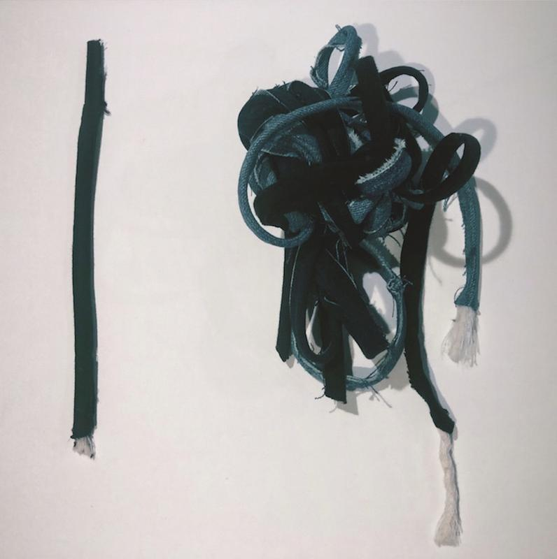 backdrop of a white canvas 2 objects made of cotton cording covered with recycled denim are placed equidistant. Left object is black denim covered cording in an imperfect straight line , the cotton cording is peaking Out of the bottom. Right object is a range of blues and black cording jumbled in a series of knots and tangles with both end exposing the cotton cording.